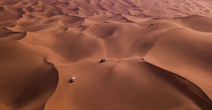 dva automobila u pustinjskoj vožnji uslikana iz ptičije perspektive